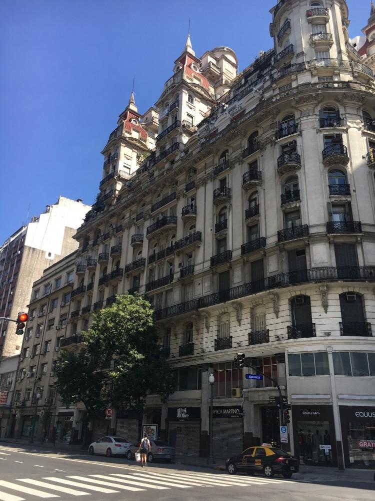 この街に特徴的な建物の前に、この街特有の黄色と黒のタクシー